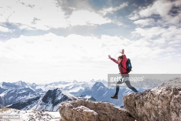 Germany, Bavaria, Oberstdorf, woman jumping on rock in alpine scenery