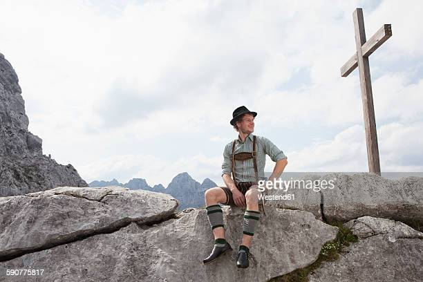 Germany, Bavaria, Osterfelderkopf, man in traditional clothes sitting at summit cross