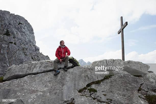 Germany, Bavaria, Osterfelderkopf, man resting at summit cross