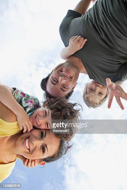 Germany, Bavaria, Parents giving children piggyback ride in park, smiling, portrait