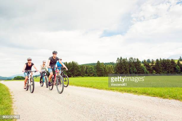 germany, bavaria, pfronten, family riding mountain bikes in the countryside - leisure equipment stock pictures, royalty-free photos & images