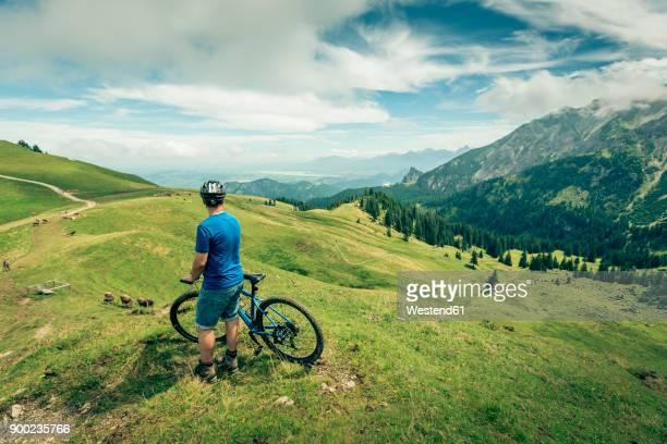 Germany, Bavaria, Pfronten, man with mountain bike on alpine meadow near Aggenstein