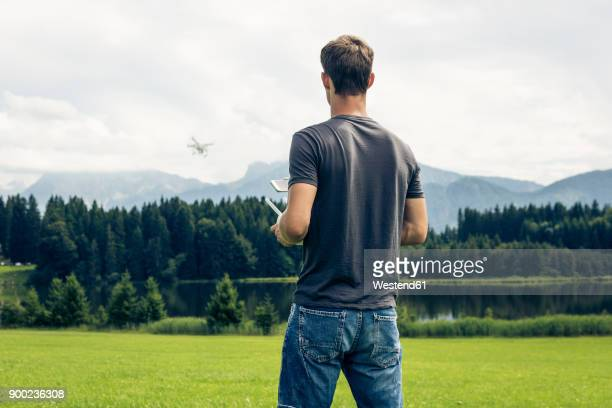 germany, bavaria, pfronten, young man flying his drone at lakeside - drone photos et images de collection