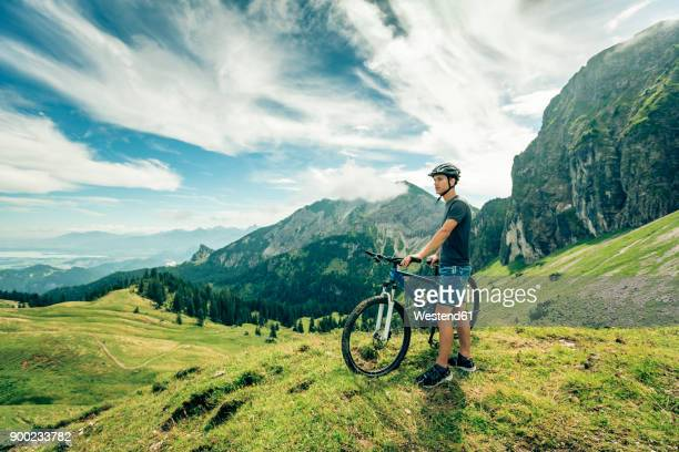 germany, bavaria, pfronten, young man with mountain bike on alpine meadow near aggenstein - bavaria stock pictures, royalty-free photos & images