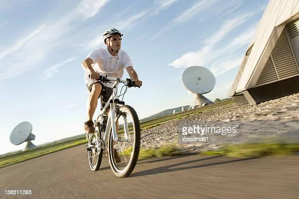 Germany, Bavaria, Raisting, Mature man riding bicycle near radio station