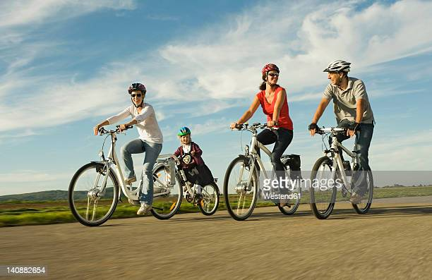 Germany, Bavaria, Raisting, People riding electric bicycle near radio station