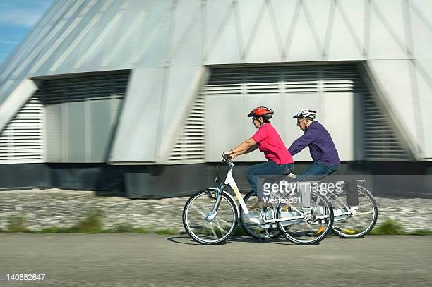 Germany, Bavaria, Raisting, Senior couple riding electric bicycle near radio station