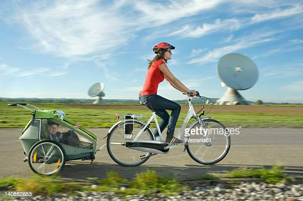 Germany, Bavaria, Raisting, Woman with girl riding child trailer near radio station