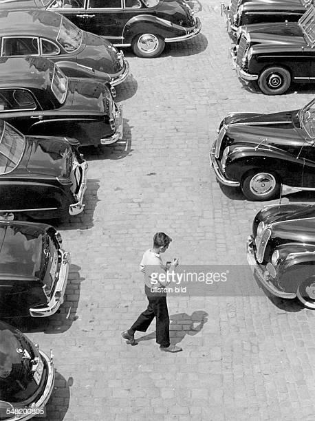 Germany Bavaria Regensburg - boy walking over a car park