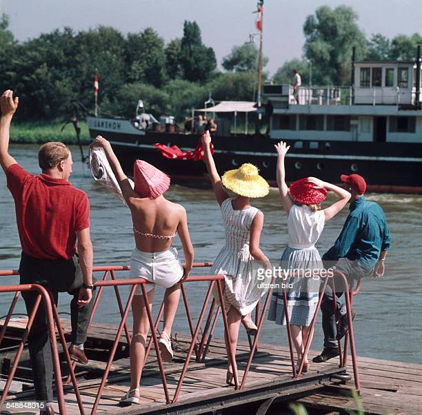 Germany Bavaria Regensburg five people on a landing stage are weaving at a ship on the Danube river 1950s