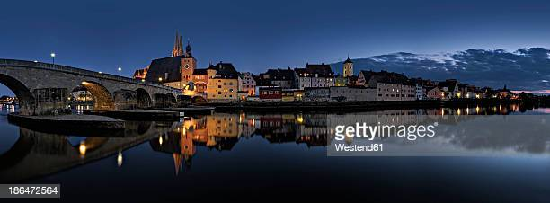 Germany, Bavaria, Regensburg, View of old town and old stone bridge crossing Danube River at night