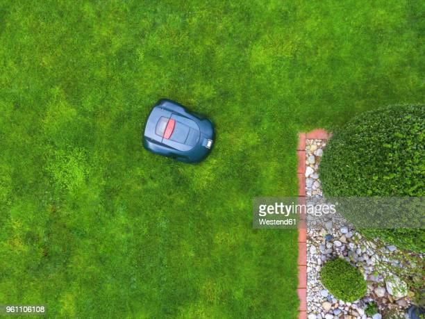 germany, bavaria, robotic lawn mower on meadow - lawn mower stock pictures, royalty-free photos & images