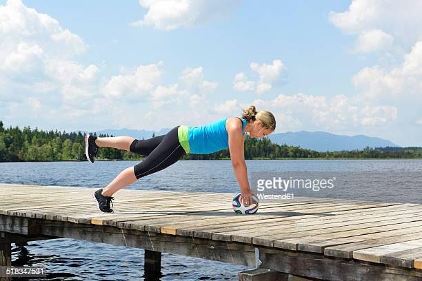 Germany, Bavaria, Sachsenkam, woman exercising functional training on jetty at sea