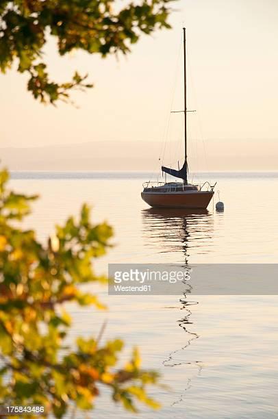 Germany, Bavaria, Sailing boat on Lake Ammersee at sunset