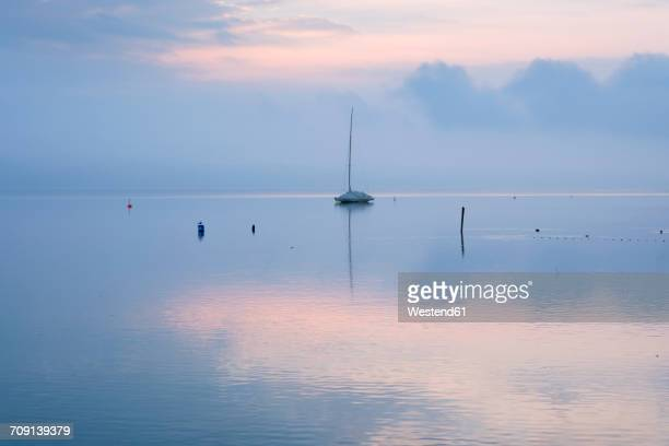 germany, bavaria, sailing boat on lake starnberg at dawn - starnberg photos et images de collection