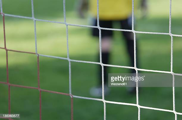 Germany, Bavaria, Schaeftlarn, Close up of football net with teenage boy goalkeeper in background