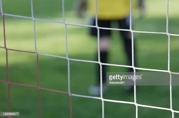 Germany, Bavaria, Schaeftlarn, Close up of football net with teenage boy goalkeeper in background