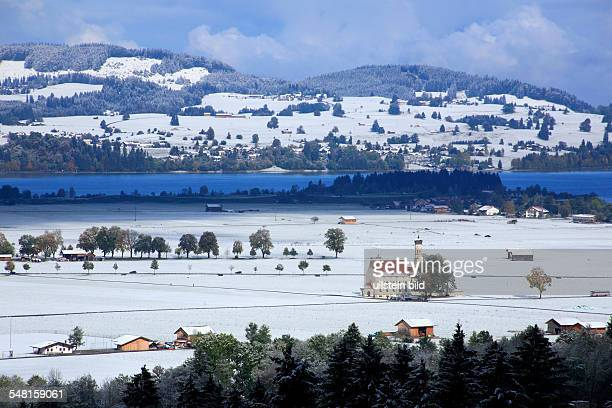 Germany Bavaria Schwangau snowcovered landscape with church 'St Coloman' and lake 'Forggensee'