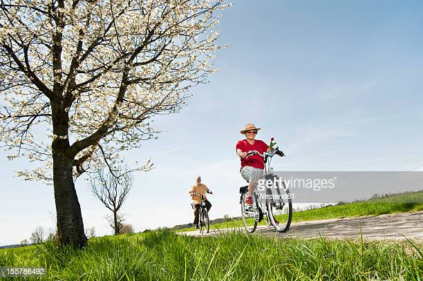 Germany, Bavaria, Senior couple riding electric bicycle