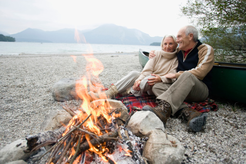 Germany, Bavaria, Senior couple sitting at campfire - gettyimageskorea