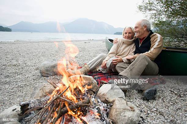 Germany, Bavaria, Walchensee, Senior couple sitting beside camp fire