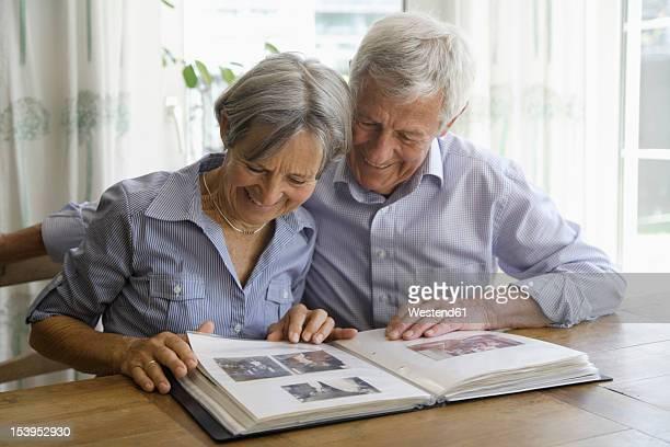 germany, bavaria, senior couple with photo album, smiling - ehefrau fotos stock-fotos und bilder