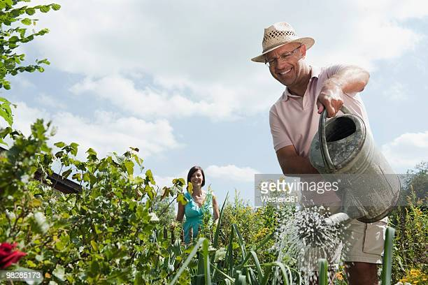 Germany, Bavaria, Mature man watering in garden, woman standing in background