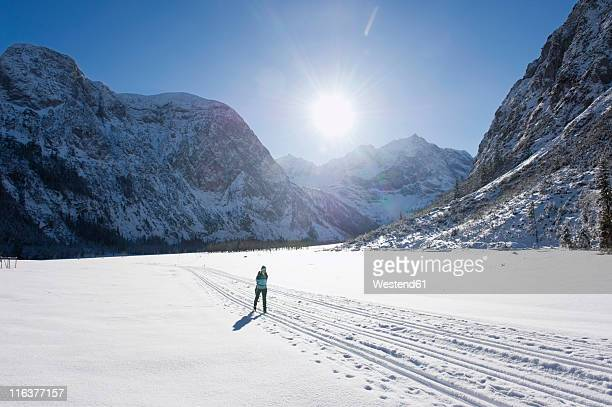 Germany, Bavaria, Senior woman doing cross-country skiing with karwendal mountains in background