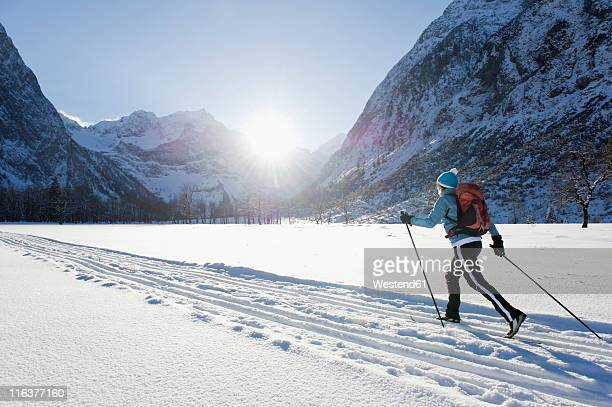 germany, bavaria, senior woman doing cross-country skiing with karwendal mountains in background - langlaufen stockfoto's en -beelden