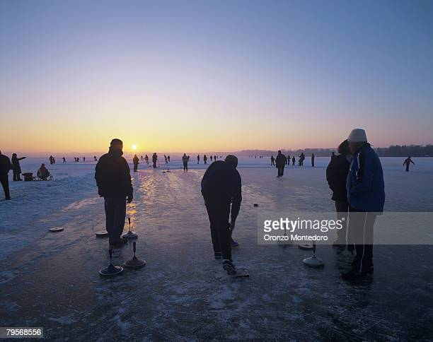 Germany, Bavaria, Amper River, silhouette of people ice curling