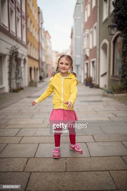 Germany, Bavaria, smiling little girl standing in an alley