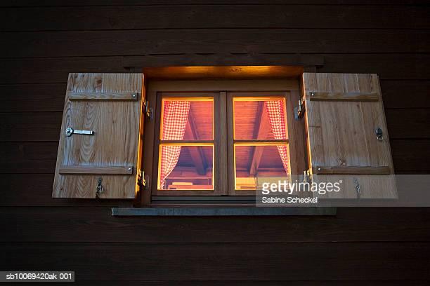 Germany, Bavaria, Spitzing, ski chalet window at dusk
