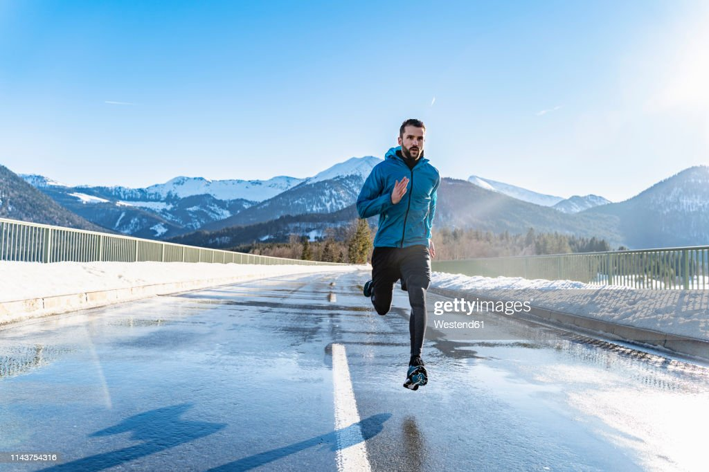 Germany, Bavaria, sportive man running on a road in winter : Stock-Foto