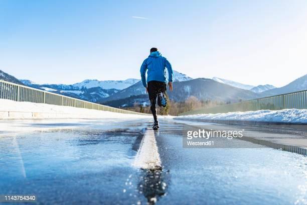 germany, bavaria, sportive man running on a road in winter - chándal fotografías e imágenes de stock