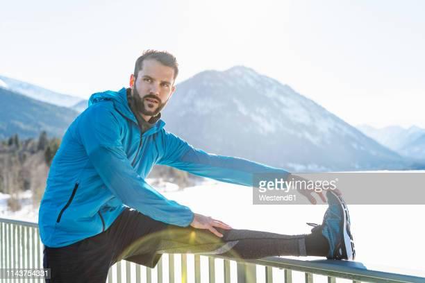 germany, bavaria, sportive man stretching in winter on bridge railing - winter sport stock-fotos und bilder