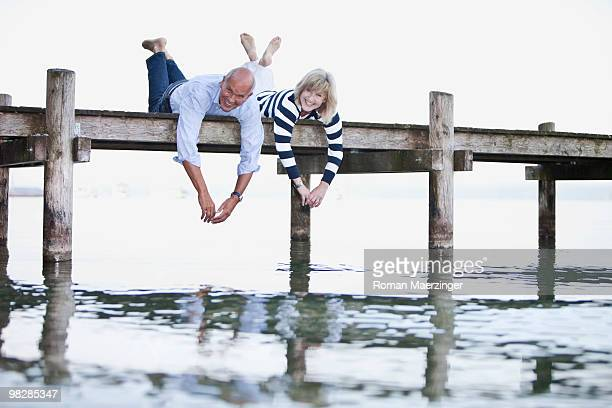 Germany, Bavaria, Starnberger See, Couple lying on jetty, smiling, portrait
