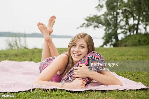Germany, Bavaria, Starnberger See, Teenage girl (16-17) lying on blanket in park, smiling, portrait