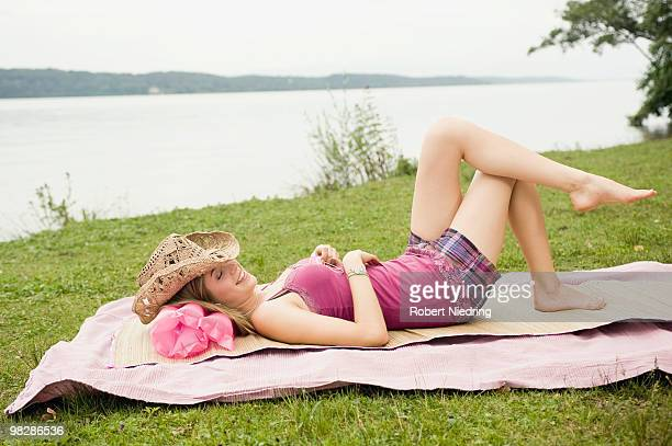 Germany, Bavaria, Starnberger See, Teenage girl (16-17) lying on blanket in park, smiling, side view