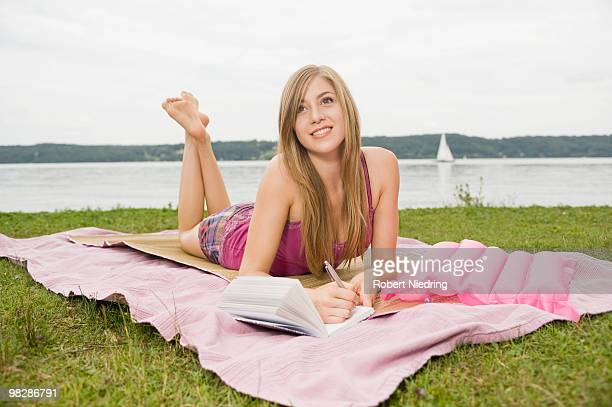 Germany, Bavaria, Starnberger See, Teenage girl (16-17) lying on blanket and writing, smiling