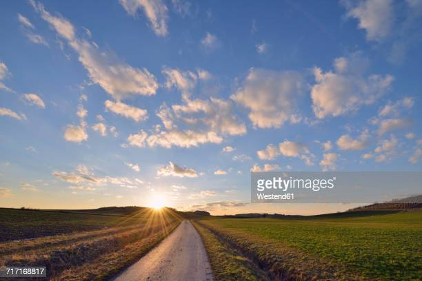 Germany, Bavaria, Sunset with small rural road through fields