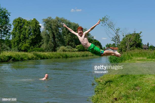 Germany, Bavaria, teenage boy jumping into River Loisach