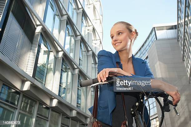 Germany, Bavaria, Teenage girl on bicycle, smiling