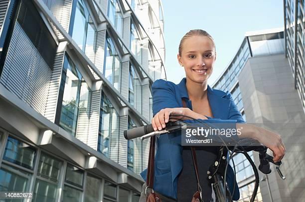 Germany, Bavaria, Teenage girl on bicycle, smiling, portrait