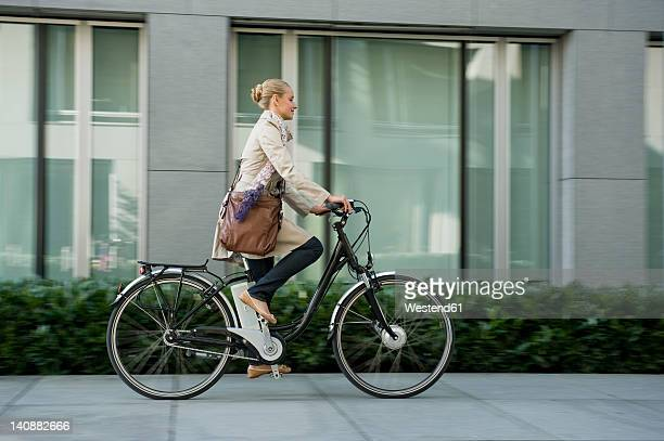 Germany, Bavaria, Teenage girl riding bicycle