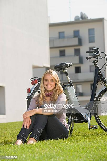 Germany, Bavaria, Teenage girl sitting in grass by bicycle, smiling, portrait