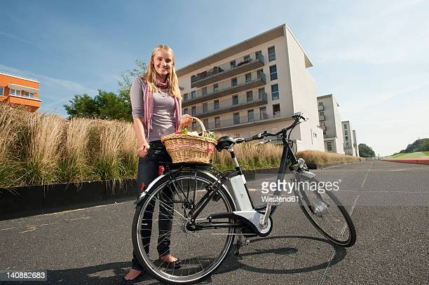 Germany, Bavaria, Teenage girl standing by bicycle holding basket, smiling, portrait