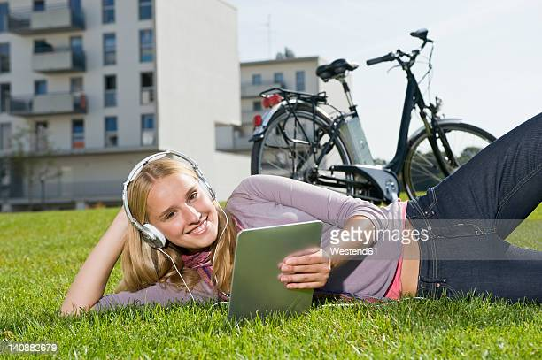 Germany, Bavaria, Teenage girl using tablet pc and listening music, smiling, portrait