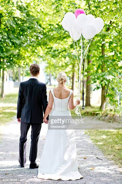 Germany, Bavaria, Tegernsee, Wedding couple walking under trees, holding balloons