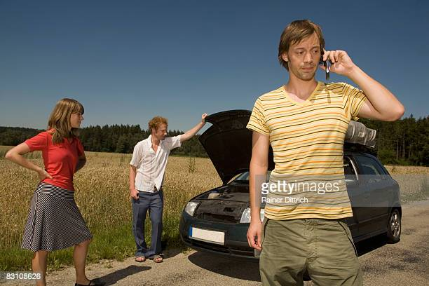 Germany, Bavaria, three friends with broken down car, man using mobile phone in foreground