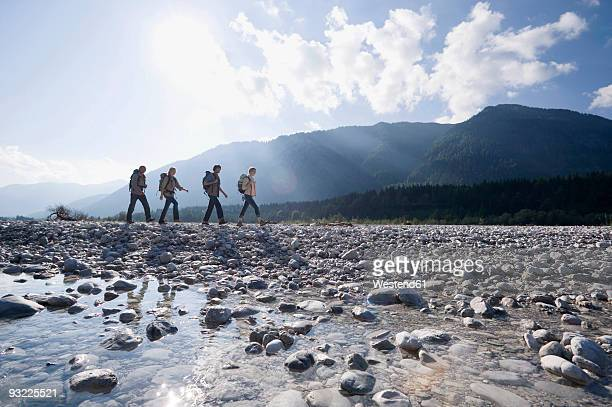 Germany, Bavaria, Toelzer Land, Group of people hiking, mountains in background, side view
